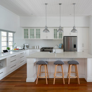Design ideas for a beach style l-shaped kitchen in Brisbane with a farmhouse sink, shaker cabinets, white cabinets, white splashback, stainless steel appliances, medium hardwood floors, with island, brown floor, grey benchtop and timber.