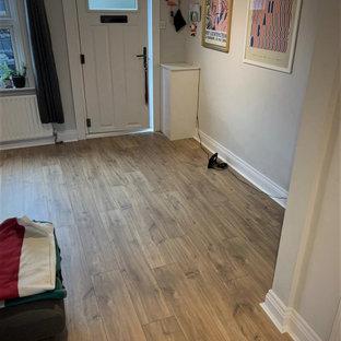 Idee per una piccola porta d'ingresso minimalista con pareti bianche, pavimento in laminato, una porta singola e pavimento marrone