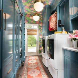 Идея дизайна: отдельная, параллельная прачечная среднего размера в стиле фьюжн с врезной раковиной, фасадами с декоративным кантом, синими фасадами, столешницей из кварцевого агломерата, синим фартуком, фартуком из плитки кабанчик, синими стенами, темным паркетным полом, со стиральной и сушильной машиной рядом, белой столешницей, потолком с обоями и обоями на стенах