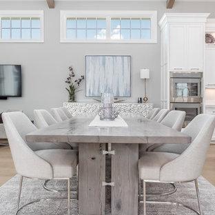 Источник вдохновения для домашнего уюта: огромная кухня-столовая в стиле модернизм с серыми стенами, светлым паркетным полом, фасадом камина из каменной кладки, бежевым полом и сводчатым потолком