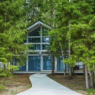 На фото: двухэтажный, белый частный загородный дом в стиле модернизм с двускатной крышей