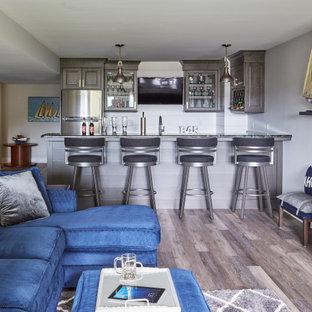 ミルウォーキーの広いビーチスタイルのおしゃれなウェット バー (コの字型、落し込みパネル扉のキャビネット、茶色いキャビネット、ラミネートカウンター、塗装板のキッチンパネル、ラミネートの床、茶色い床、茶色いキッチンカウンター) の写真