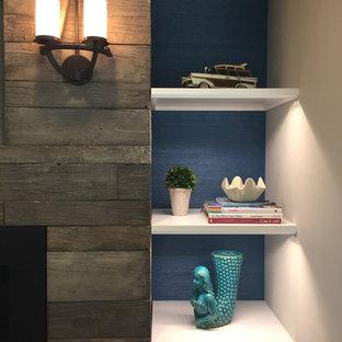Imagen de sala de estar abierta, marinera, pequeña, con paredes blancas, chimenea lineal, marco de chimenea de madera y televisor colgado en la pared