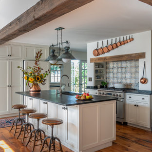 Farmhouse kitchen designs - Example of a farmhouse light wood floor and exposed beam kitchen design in Boston with white cabinets, stainless steel appliances, an island and black countertops
