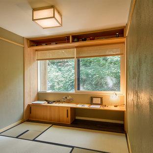 Home studio - mid-sized built-in desk dark wood floor home studio idea in New York with green walls