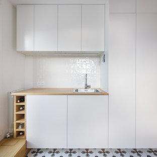 Idéer för ett mellanstort modernt beige linjärt grovkök, med en nedsänkt diskho, luckor med profilerade fronter, vita skåp, träbänkskiva, vitt stänkskydd, stänkskydd i terrakottakakel, vita väggar, klinkergolv i keramik, tvättmaskin och torktumlare byggt in i ett skåp och flerfärgat golv