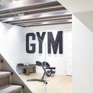 Kleiner Moderner Fitnessraum mit weißer Wandfarbe, Laminat, weißem Boden und freigelegten Dachbalken in Toronto