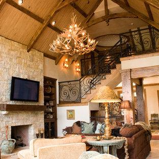 Diseño de sala de estar abierta, rural, grande, con paredes beige, suelo de travertino, chimenea tradicional, marco de chimenea de piedra y televisor colgado en la pared