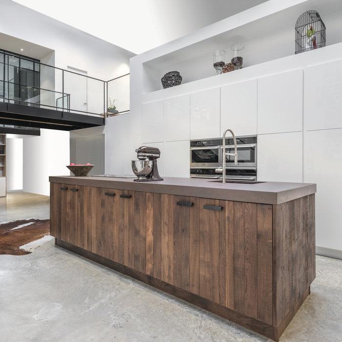 Esprit loft contemporain pour cette cuisine au sol en béton ciré : l'escalier associe métal et  bois ; la cuisine est réalisée en planches de Chêne massif à nœuds, défibré et traité dans un esprit « v
