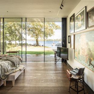Modernes Schlafzimmer mit weißer Wandfarbe, braunem Holzboden und braunem Boden in Hannover