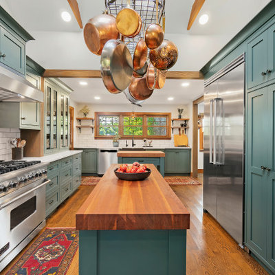 Example of a large classic u-shaped medium tone wood floor and exposed beam enclosed kitchen design in Providence with a farmhouse sink, shaker cabinets, green cabinets, white backsplash, subway tile backsplash, stainless steel appliances, two islands and white countertops
