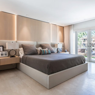 This is an example of a mid-sized contemporary master bedroom in Miami with limestone floors, white walls and grey floor.