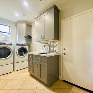 Inredning av en klassisk mellanstor vita l-formad vitt tvättstuga enbart för tvätt, med en undermonterad diskho, skåp i shakerstil, grå skåp, bänkskiva i kvartsit, vitt stänkskydd, stänkskydd i keramik, grå väggar, travertin golv, en tvättmaskin och torktumlare bredvid varandra och beiget golv