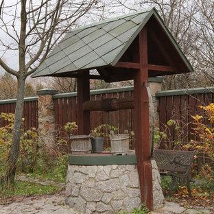 Immagine di un giardino country dietro casa con fontane e pavimentazioni in pietra naturale