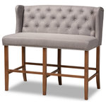 Wholesale Interiors - Alira Modern Contemporary Grey Fabric Walnut Wood Button Tufted Bar Stool Bench - Host happy hour in your home with the Alira bar stool bench. Constructed from wood, this bench provides solid seating for two. The seat and back are upholstered in a soft neutral fabric and padded with foam for endless comfort. A built-in foot rest provides additional seating comfort. Elaborate button tufting on the back gives this bench a refined look, while silver nail heads highlight the elegant wingback silhouette. The Alira is well suited for both a kitchen or bar setting. The Alira bar stool bench is made in Malaysia and requires assembly.