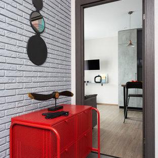 Industriell inredning av en mellanstor entré, med vita väggar, klinkergolv i porslin och brunt golv
