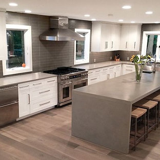 Large transitional kitchen pantry inspiration - Inspiration for a large transitional l-shaped medium tone wood floor kitchen pantry remodel in Orlando with a farmhouse sink, shaker cabinets, white cabinets, concrete countertops, gray backsplash, stainless steel appliances and an island