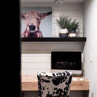 Kleines Landhausstil Arbeitszimmer mit weißer Wandfarbe, Teppichboden, Einbau-Schreibtisch, grauem Boden und Holzdielenwänden in Minneapolis