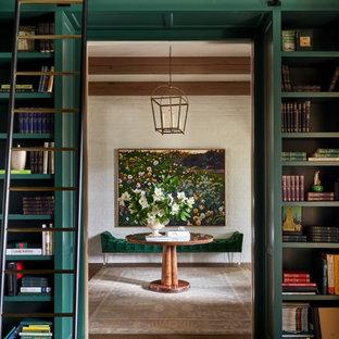 他の地域の広いトランジショナルスタイルのおしゃれなホームオフィス・書斎 (ライブラリー、緑の壁、無垢フローリング、標準型暖炉、積石の暖炉まわり、自立型机、茶色い床、表し梁、レンガ壁) の写真
