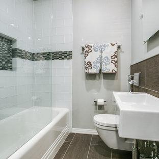 Ispirazione per una piccola stanza da bagno chic con vasca/doccia, WC monopezzo, piastrelle bianche, piastrelle di vetro, pareti grigie, pavimento in gres porcellanato e lavabo sospeso