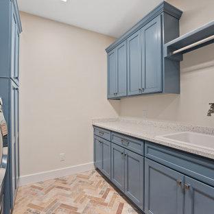 Lantlig inredning av en stor flerfärgade parallell flerfärgat tvättstuga enbart för tvätt, med en nedsänkt diskho, skåp i shakerstil, blå skåp, bänkskiva i återvunnet glas, beige väggar, tegelgolv, en tvättmaskin och torktumlare bredvid varandra och flerfärgat golv