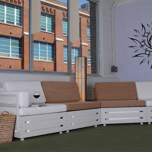 Cette photo montre une salle de séjour mansardée ou avec mezzanine moderne de taille moyenne avec un mur violet, béton au sol, aucune cheminée, aucun téléviseur et un sol vert.