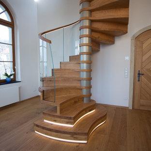 Imagen de escalera de caracol y papel pintado, contemporánea, grande, con escalones de madera, contrahuellas de madera, barandilla de vidrio y papel pintado