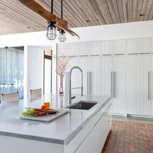 Свежая идея для дизайна: п-образная кухня среднего размера в стиле рустика с обеденным столом, врезной раковиной, фасадами с филенкой типа жалюзи, белыми фасадами, столешницей из акрилового камня, техникой из нержавеющей стали, полом из терракотовой плитки, островом, оранжевым полом, белой столешницей и деревянным потолком - отличное фото интерьера