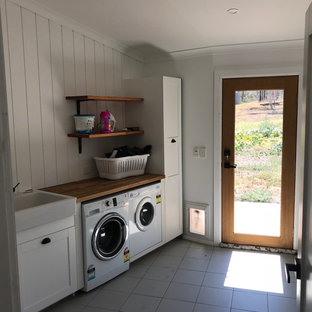 Design ideas for a mid-sized modern single-wall dedicated laundry room in Central Coast with an utility sink, recessed-panel cabinets, white cabinets, wood benchtops, white walls, ceramic floors, a side-by-side washer and dryer, grey floor and brown benchtop.
