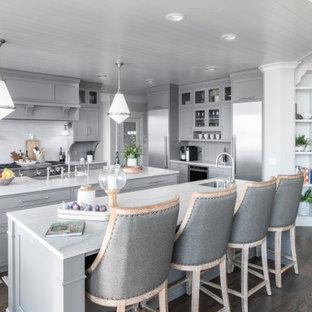 Inspiration för ett mycket stort vintage vit vitt kök, med grå skåp, bänkskiva i kvartsit, grått stänkskydd, stänkskydd i kalk, rostfria vitvaror, flera köksöar, en rustik diskho, luckor med infälld panel, mellanmörkt trägolv och brunt golv