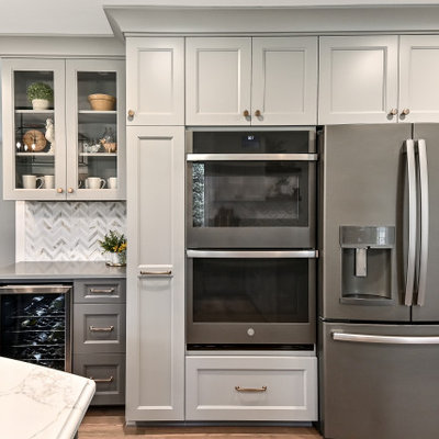 Inspiration for a huge farmhouse l-shaped medium tone wood floor and brown floor eat-in kitchen remodel in Milwaukee with a farmhouse sink, shaker cabinets, gray cabinets, quartz countertops, white backsplash, marble backsplash, stainless steel appliances, an island and gray countertops