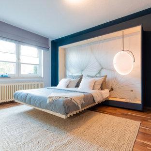 Mittelgroßes Modernes Hauptschlafzimmer mit blauer Wandfarbe, Laminat, braunem Boden, Tapetendecke und Tapetenwänden in Düsseldorf
