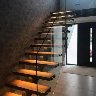 Imagen de escalera suspendida y papel pintado, minimalista, de tamaño medio, con escalones de madera, contrahuellas de metal, barandilla de vidrio y papel pintado
