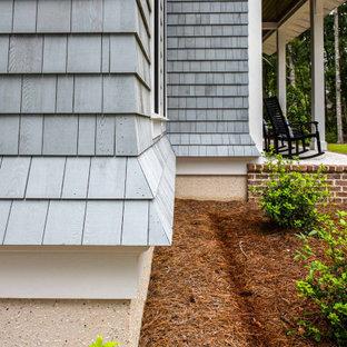 На фото: двухэтажный, серый частный загородный дом с комбинированной облицовкой, металлической крышей, серой крышей и отделкой дранкой с