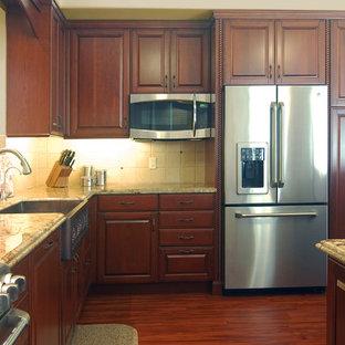 サンルイスオビスポの大きい地中海スタイルのおしゃれなキッチン (エプロンフロントシンク、レイズドパネル扉のキャビネット、赤いキャビネット、御影石カウンター、ベージュキッチンパネル、石タイルのキッチンパネル、シルバーの調理設備の、濃色無垢フローリング) の写真