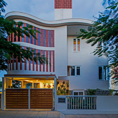 Example of a trendy gray three-story house exterior design in Bengaluru