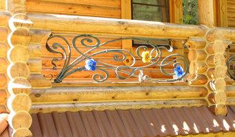Кованое ограждение балкона в деревянном доме с витражными цветами