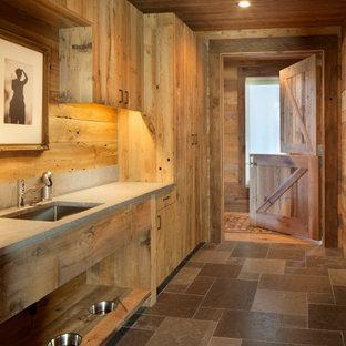 Foto på ett stort funkis grå parallellt grovkök, med en nedsänkt diskho, släta luckor, skåp i ljust trä, bänkskiva i betong, stänkskydd i trä, skiffergolv och en tvättpelare