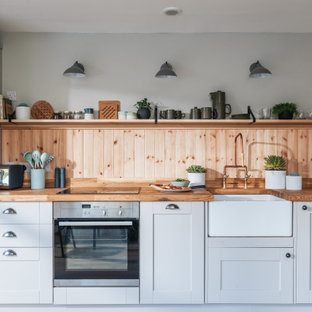 Inspiration for a medium sized rustic open plan kitchen in Hampshire with a belfast sink, recessed-panel cabinets, beige cabinets, wood worktops, wood splashback, stainless steel appliances and light hardwood flooring.