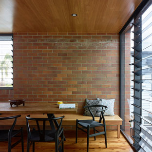 Photo of a mid-sized midcentury open plan dining in Brisbane with white walls, light hardwood floors, brown floor, timber and brick walls.