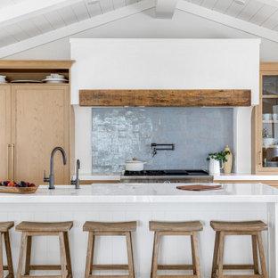 Inredning av ett maritimt litet vit linjärt vitt kök med öppen planlösning, med skåp i shakerstil, skåp i ljust trä, bänkskiva i kvarts, blått stänkskydd, stänkskydd i terrakottakakel, integrerade vitvaror och en köksö