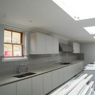 ロンドンの大きいモダンスタイルのおしゃれなキッチン (アンダーカウンターシンク、フラットパネル扉のキャビネット、グレーのキャビネット、クオーツストーンカウンター、グレーのキッチンパネル、セラミックタイルのキッチンパネル、シルバーの調理設備の、磁器タイルの床、ピンクのキッチンカウンター) の写真
