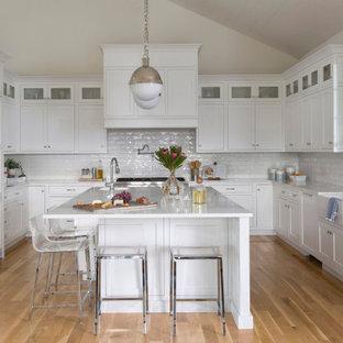 Bild på ett stort maritimt vit vitt u-kök, med en rustik diskho, vita skåp, vitt stänkskydd, integrerade vitvaror, ljust trägolv och en köksö