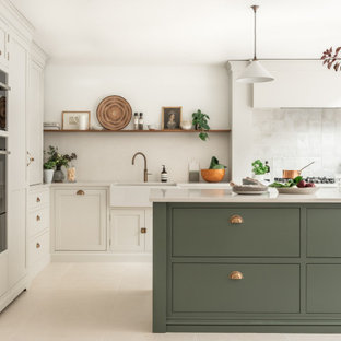Große Klassische Wohnküche in L-Form mit Landhausspüle, Schrankfronten im Shaker-Stil, grünen Schränken, Quarzit-Arbeitsplatte, Küchenrückwand in Weiß, Rückwand aus Steinfliesen, schwarzen Elektrogeräten, Keramikboden, Kücheninsel, beigem Boden und weißer Arbeitsplatte in Surrey