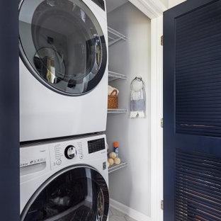 Immagine di un piccolo ripostiglio-lavanderia chic con paraspruzzi grigio, pareti grigie, pavimento in gres porcellanato, lavatrice e asciugatrice a colonna e pavimento bianco