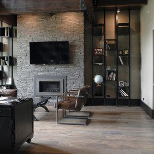 シカゴの巨大なインダストリアルスタイルのおしゃれな書斎 (白い壁、無垢フローリング、標準型暖炉、石材の暖炉まわり、自立型机、茶色い床、表し梁) の写真