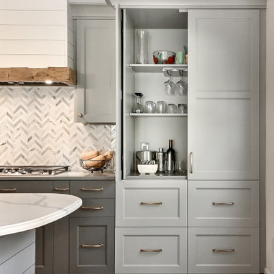Inspiration for a huge cottage l-shaped medium tone wood floor and brown floor eat-in kitchen remodel in Milwaukee with a farmhouse sink, shaker cabinets, gray cabinets, quartz countertops, white backsplash, marble backsplash, stainless steel appliances, an island and gray countertops