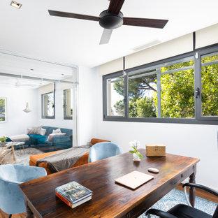 Ejemplo de despacho blanco, actual, de tamaño medio, sin chimenea, con paredes blancas, suelo de madera en tonos medios, escritorio independiente y suelo marrón