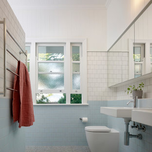 Design ideas for a mid-sized contemporary master bathroom in Brisbane with an open shower, blue tile, white walls, a wall-mount sink, tile benchtops, grey floor, a hinged shower door, white benchtops and a double vanity.