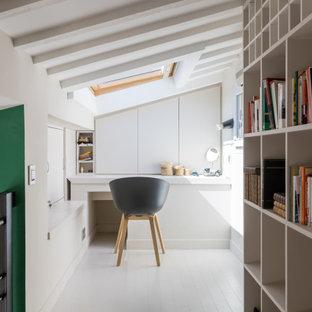 Bild på ett litet eklektiskt hemmabibliotek, med vita väggar, målat trägolv, ett inbyggt skrivbord och vitt golv